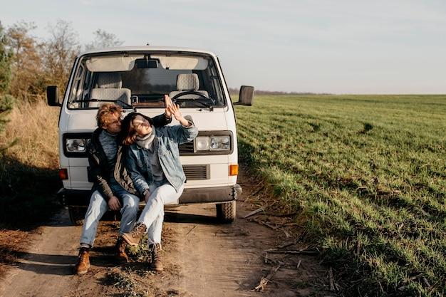 Mann und frau schauen neben ihrem van mit kopierraum auf