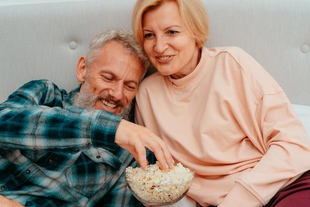 Mann und frau schauen sich einen film auf dem bett an und essen popcorn