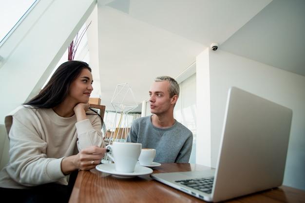 Mann und frau schauen sich interessiert an, während sie zeit in einem café verbringen. verschwommener moderner laptop auf der vorderseite. geräumiges helles café im hintergrund. attraktives junges paar.