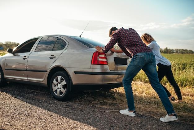 Mann und frau schieben ein kaputtes auto, rückansicht