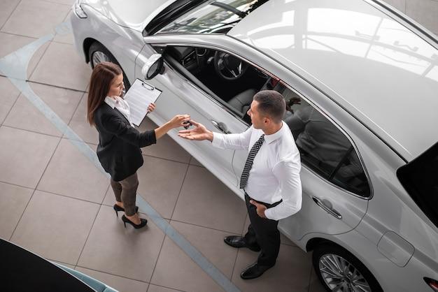 Mann und frau schließen deal bei autohaus