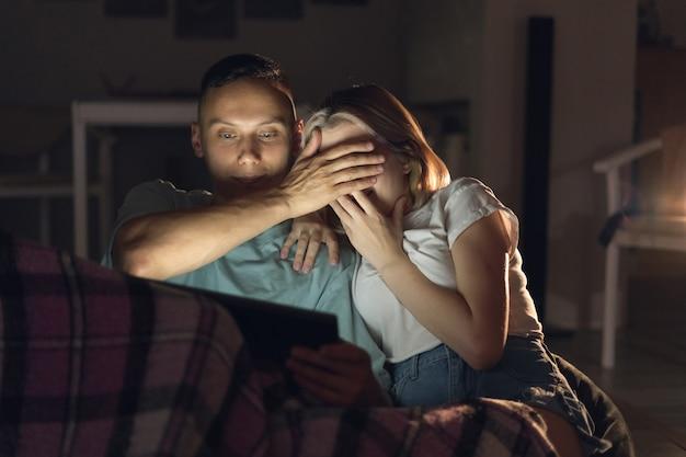 Mann und frau sitzen abends zu hause