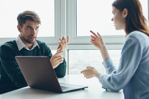 Mann und frau sitzen an einem tisch vor einem laptop und reden über arbeit