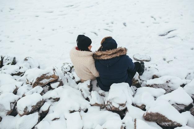 Mann und frau sitzen auf den mit schnee bedeckten felsen am ufer des sees