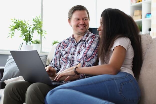 Mann und frau sitzen auf der couch mit laptop