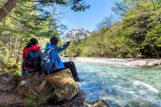 Mann und frau sitzen auf felsen nahe azusa-fluss bei kamikochi in nordjapan-alpen.