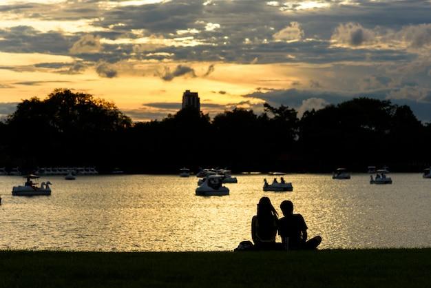 Mann und frau sitzen auf grünem glasfeld am ufer des thailand-sees während sonnenuntergang