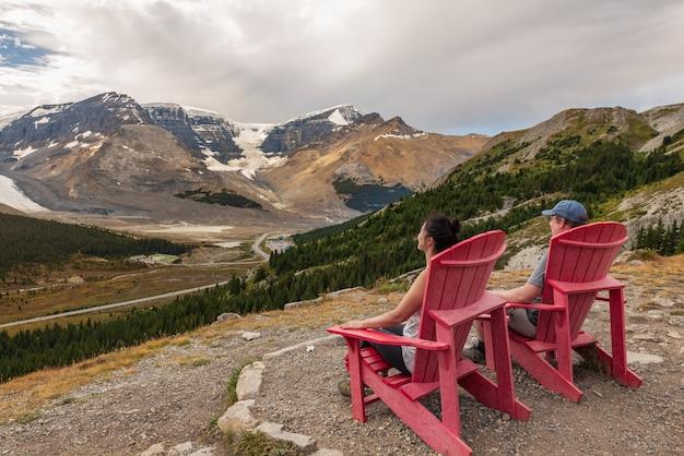 Mann und frau sitzen auf roten stühlen, die die ansicht von wilcox-spur im jasper-nationalpark, alberta, kanada einnehmen.