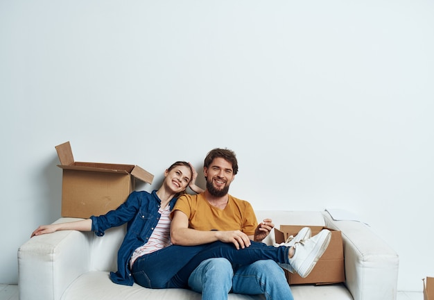 Mann und frau sitzen auf weißen couchboxen mit bewegenden lifestyle-dingen