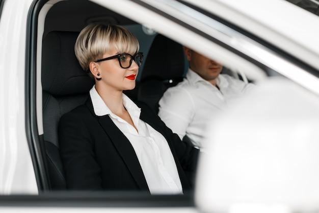 Mann und frau sitzen in einem autosalon. nahaufnahmeportrait der frau.