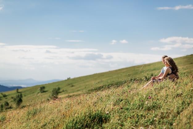 Mann und frau sitzen, umarmend auf dem gras vor schöner landschaft