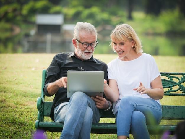 Mann und frau sitzen und benutzen computerlaptop im park