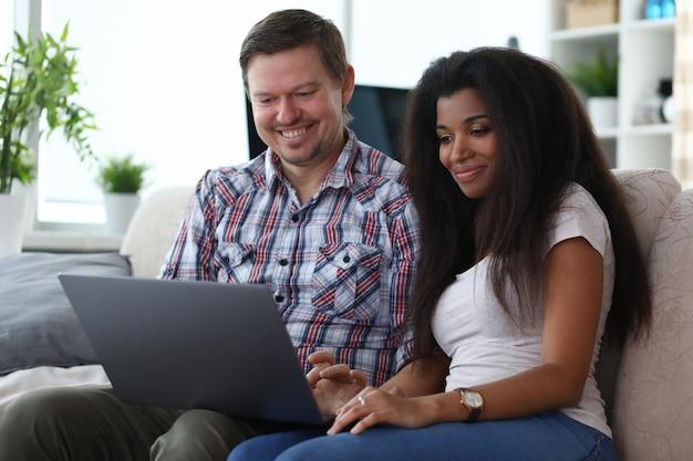 Mann und frau sitzen zu hause auf der couch mit laptop und lächeln
