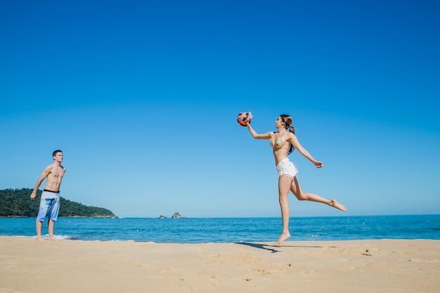 Mann und frau spielen beach-volleyball