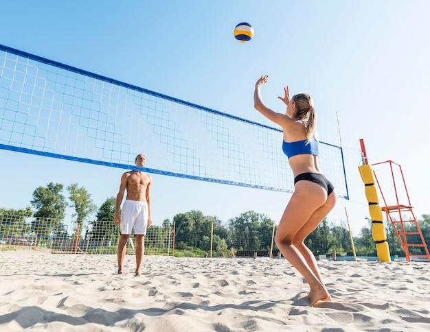 Mann und frau spielen beachvolleyball