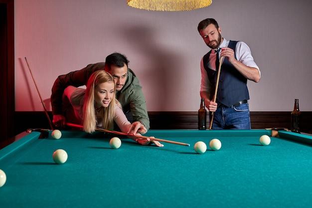 Mann und frau spielen billard, ein mann bringt einer frau das billard bei. unterhaltung, urlaubskonzept