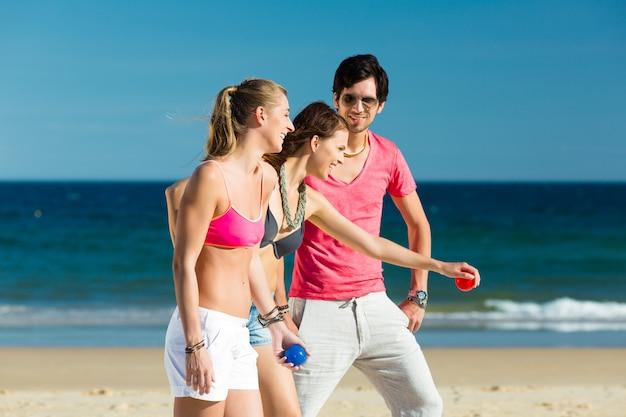 Mann und frau spielen boule am strand