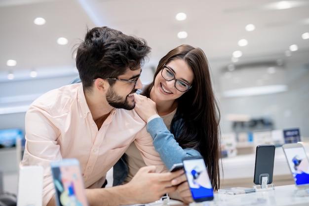 Mann und frau sprechen darüber, welches smartphone sie kaufen sollen. mann, der in den händen smartphone hält, während frau sich auf ihn stützt.