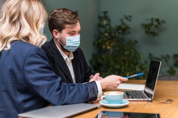 Mann und frau sprechen über ein neues projekt, während sie medizinische masken tragen