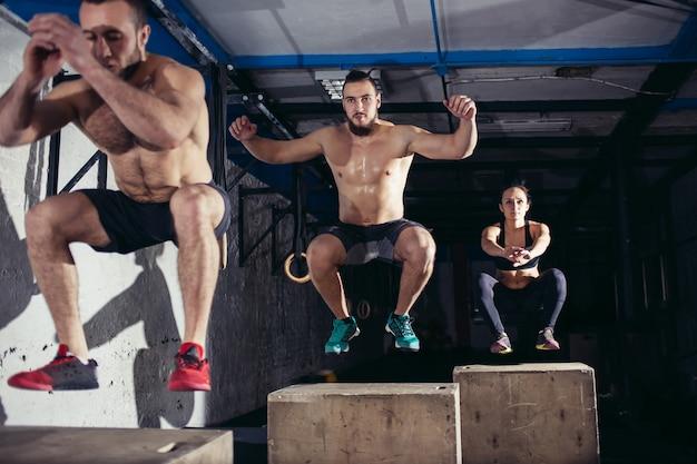 Mann und frau springen auf fitbox im fitnessstudio