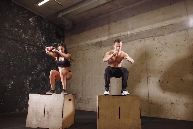 Mann und frau springen auf fitbox