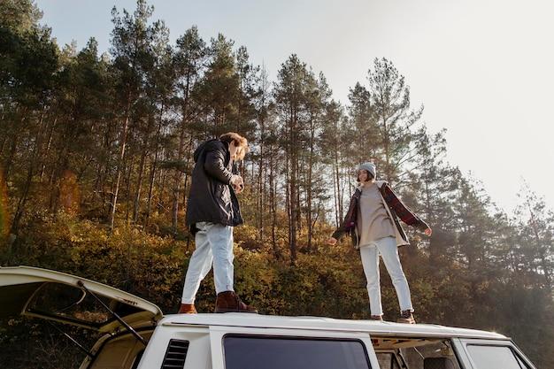 Mann und frau stehen auf einem van im freien
