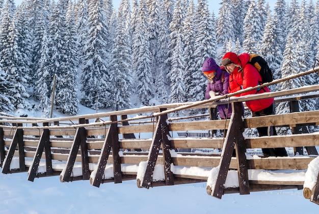 Mann und frau stehen im winter auf einer hölzernen hängebrücke