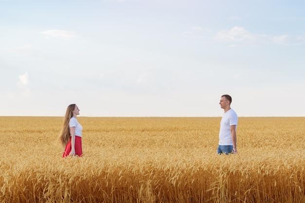 Mann und frau stehen in einiger entfernung auf dem weizenfeld. leute im feld auf himmelhintergrund