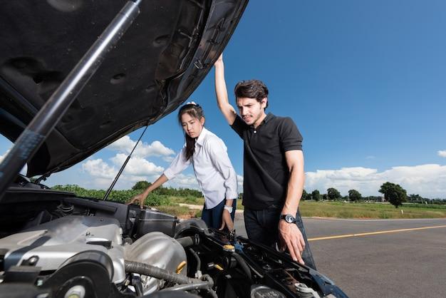 Mann und frau stehen neben dem kaputten auto und wissen nicht, was sie tun sollen