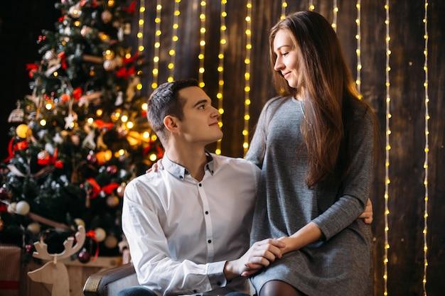 Mann und frau stehen vor einem weihnachtsbaum in einem gemütlichen zimmer