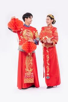 Mann und frau tragen cheongsam lächelnd, um mit schöner roter lampe und geschenkgeld zu bekommen
