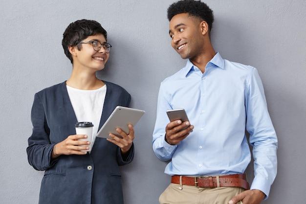 Mann und frau tragen formelle kleidung und halten telefon und tablette