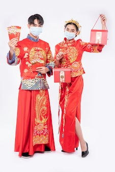 Mann und frau tragen maske und cheongsam mit rotem geschenkgeld und roter tasche