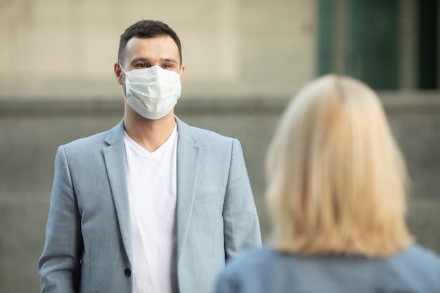 Mann und frau tragen schützende gesichtsmasken, die 2 m voneinander entfernt stehen und soziale distanz halten, um die ausbreitung des coronavirus zu vermeiden