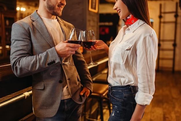 Mann und frau trinken rotwein an der theke