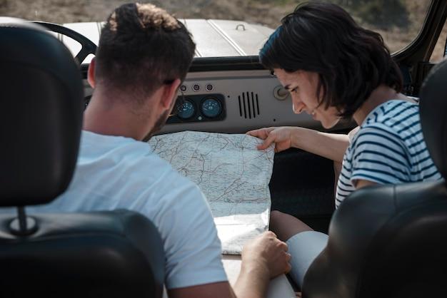 Mann und frau überprüfen karte zusammen, während sie mit dem auto reisen