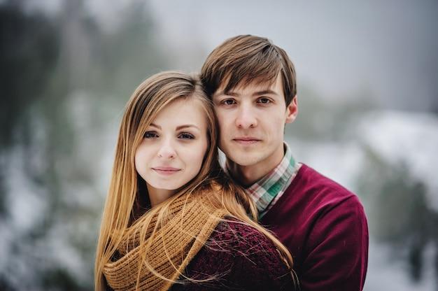 Mann und frau umarmen sich am valentinstag. junges romantisches paar hat spaß draußen im winterpark vor weihnachten. genießen sie die gemeinsame zeit in silvester.