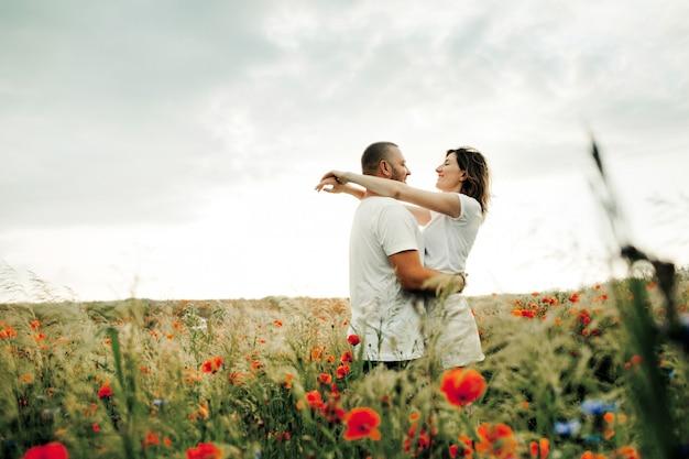 Mann und frau umarmen sich und stehen zwischen dem schönen mohnfeld