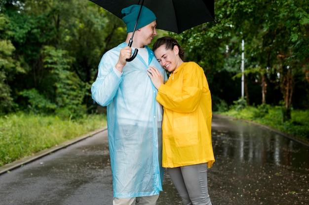 Mann und frau umarmen sich unter dem regenschirm