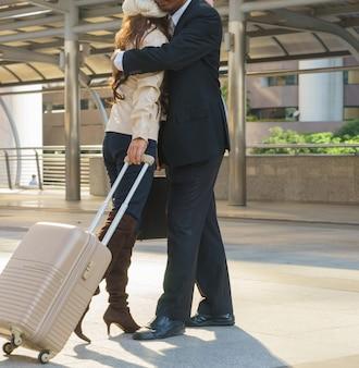 Mann und frau umarmen sich vor der reise