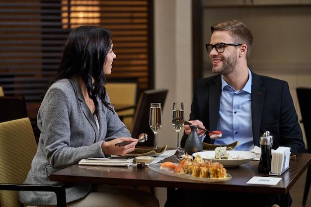 Mann und frau unterhalten sich beim gemeinsamen abendessen, während sie sushi-rollen mit essstäbchen aufnehmen