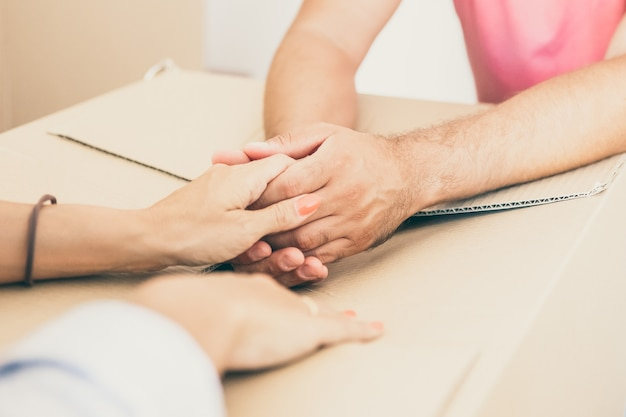 Mann und frau unterstützen sich gegenseitig und halten hände über pappkarton, während sie in die neue wohnung ziehen.