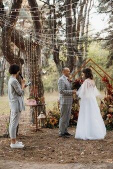 Mann und frau verlobten sich im herbstwald bei einer geschmückten hochzeitszeremonie