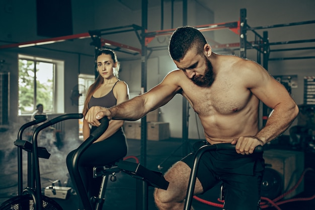 Mann und frau während der übungen im fitnessstudio.