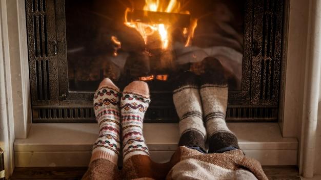 Mann und frau wärmen und entspannen sich am kamin an einem kalten tag