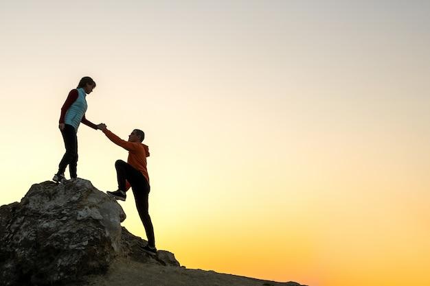 Mann und frau wanderer helfen sich gegenseitig, einen großen stein bei sonnenuntergang in den bergen zu besteigen. paar klettern auf einem hohen felsen in der abendnatur. konzept für tourismus, reisen und gesunden lebensstil.