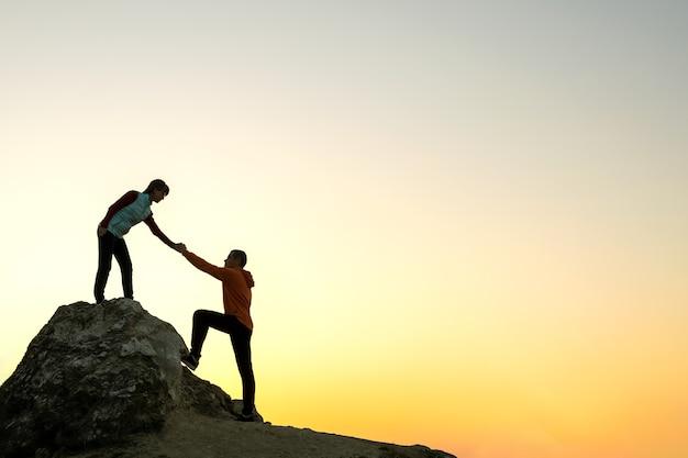 Mann und frau wanderer helfen sich gegenseitig, einen großen stein bei sonnenuntergang in den bergen zu besteigen