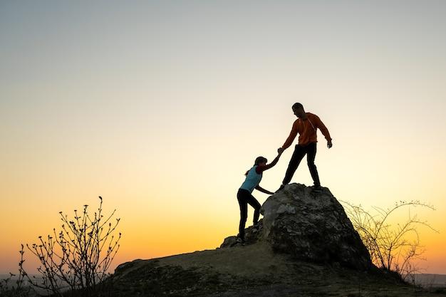 Mann und frau wanderer helfen sich gegenseitig, einen großen stein bei sonnenuntergang in den bergen zu erklimmen.