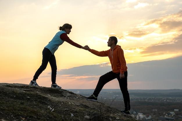 Mann und frau wanderer helfen sich gegenseitig, stein bei sonnenuntergang in bergen zu klettern. paar, das auf hohem felsen in der abendnatur klettert. konzept für tourismus, reisen und gesunden lebensstil.
