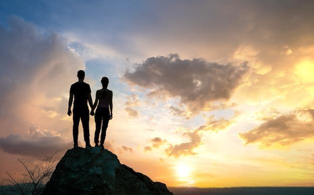 Mann und frau wanderer stehen auf einem großen stein bei sonnenuntergang in den bergen